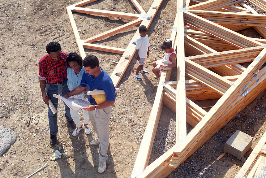 Family checks house plans with builder during house consruction
