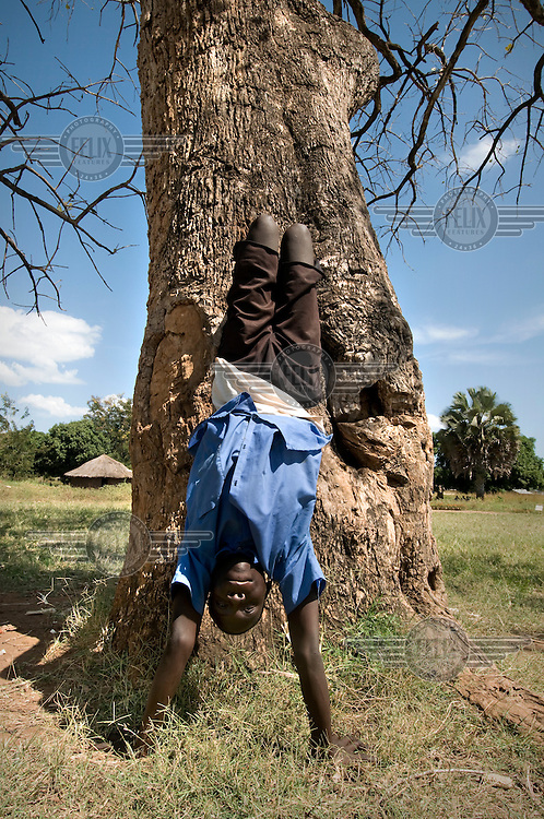 A schoolboy practises handstands against a tree.