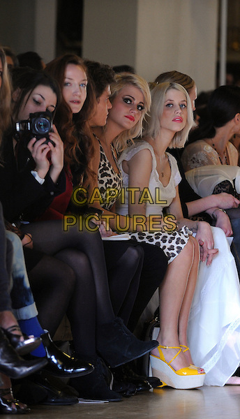 Pixie Lott (Victoria Louise Lott), Peaches Geldof .at London Fashion Week, Somerset House, London, England, UK,.18th February 2012 .LFW full length sleeveless print dress cream brown  yellow open toe sandals shoes sitting front row wedges .CAP/WIZ.© Wizard/Capital Pictures.
