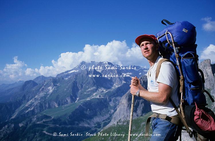 Male hiker contemplating a mountainous landscape.