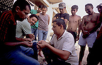 Inmigrants from Central America in Chiapas, Southern Mexico, before boarding a train in their attempt to reach the US border. They are the poorest persons among the inmigrants, they got to Mexico walking from Honduras, Guatemala or Nicaragua. Once in Mexico they can rest in shelters run by catholic priests before facing the dangerous train travel. In this step, they are often abused by police and gangs that steal the men and rape the women..Migrantes centroamericanos juegan y se distraen en el albergue ¨Hogar de la Misericordia¨en Arriaga, Chiapas, lugar donde subirán al tren para continuar su camino a la frontera norte de México.