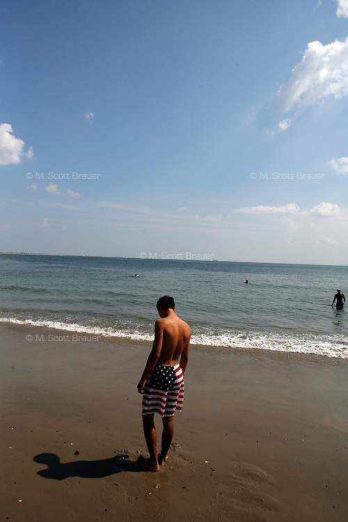 A man wears American flag swimming trunks on the beach at Coney Island, Brooklyn, New York, USA.