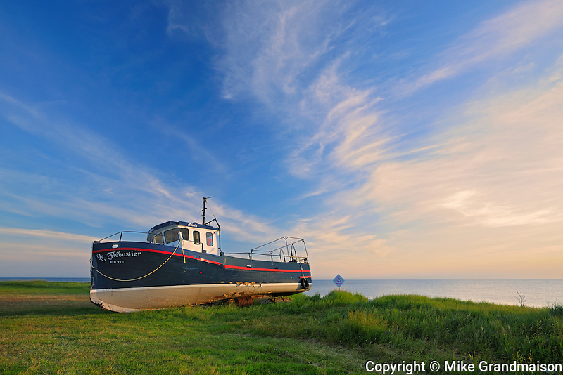 old fishing boat and clouds on shore of Gulf of St. Lawrence<br /> Cape Chat<br /> Quebec<br /> Canada