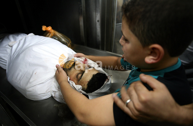 The son of Palestinian Islamic Jihad militant Ismael Al-Asmar mourn over his body at Rafah hospital after an Israeli air strike hit his car in Rafah in the southern Gaza Strip on 24 August 2011. Al-Asmar, one of the militant leaders of the Islamic Jihad group, was killed during the strike. Photo by Ali Jadallah