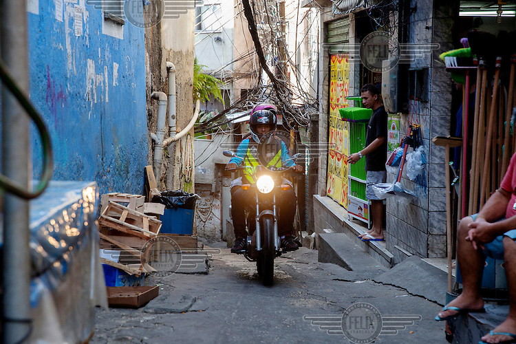 26 year old Felipe Ribas has been working as a 'moto-taxi' driver for eight years, helping people overcome the Rocinha favela's complex geography and narrow alleyways to reach their destination. When he is not working Felipe is a percussionist playing with various groups in the area.