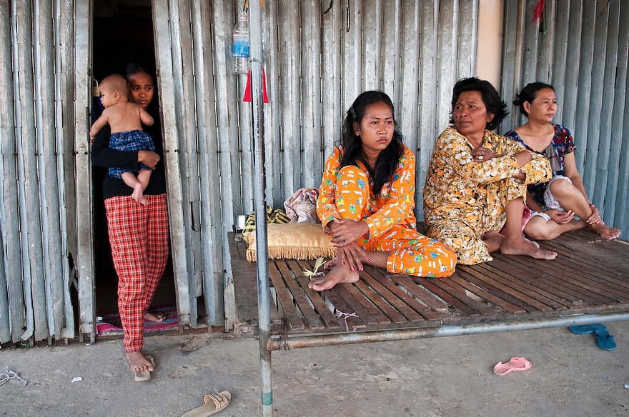 PHNOM PENH, CAMBODIA--Evicted from their homes in Phnom Penh, a group of women sit together outside unfinished homes at Damnak Trayeueng, a relocation site 16 kilometers from the city center. PHOTO BY JODI HILTON .