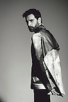Young man with dark hair and well kept beard on fashion shoot in studio