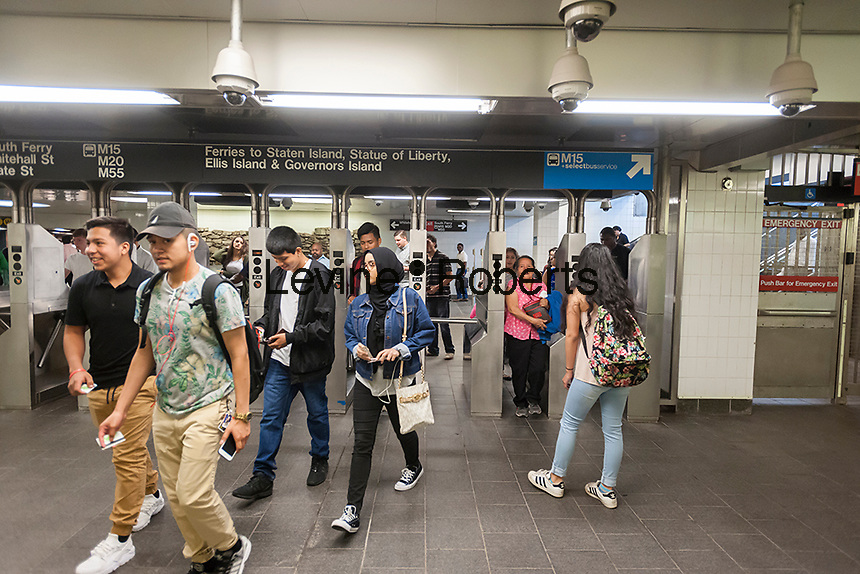 Passengers swipe through the turnstiles in the newly restored South Ferry subway station in New York on re-opening day Tuesday, June 27, 2017. The restored station was closed after catastrophic damage by Superstorm Sandy with an estimated 15 million gallons of water flooding the terminal which cost $545 million and was only open three years. The $340 million in repairs were finished today nearly five years after Superstorm Sandy. In the interim the Number One train used the quirky old South Ferry loop which only accommodated the first five cars of a ten car train.  (© Richard B. Levine)