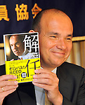 April 19, 2012, Tokyo, Japan - Michael Woodford shows a copy of the book he wrote about the $1.7 billion cover-up by Olympic Corp. and his dismissal as its president during a news conference at Tokyos Foreign Correspondents Club of Japan on Thursday, April 19, 2012...Woodford said hell attend an extraordinary meeting Friday of Olympus shareholders, who are likely to back a slate of management-proposed directors and let the camera maker put behind it the accounting fraud. (Photo by Natsuki Sakai/AFLO) AYF -mis-.