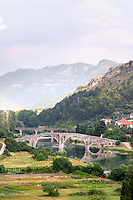 An old Roman stone bridge across the river Trebisnjica. Houses. against a mountain backdrop. Trebinje. Republika Srpska. Bosnia Herzegovina, Europe.