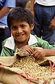 San Juan del Oro, Peru. Young boy with open bag of  coffee.