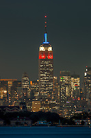 The Empire State Building at twilight, as viewed from the south over Ellis Island in New York Harbor on Tuesday, September 11, 2012. The Empire State Building was illuminated in red, white, and blue in memory of the events of September 11, 2001.