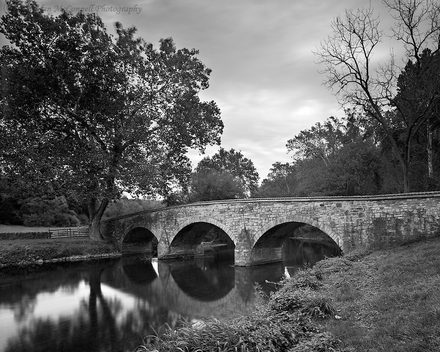 """""""Burnside Bridge""""<br /> Antietam National Battlefield<br /> Sharpsburg, Maryland<br />  2014<br /> Peaceful waters reflect the sturdy limestone arches of Burnside Bridge, located southeast of Sharpsburg, Maryland.   Built in 1836 as a crossing of Antietam Creek, the bridge witnessed the daunting task of a Union attack on the Confederate infantry and artillery in 1862.  A sycamore tree provides a respite just as it did for battle-weary soldiers over 150 years ago."""