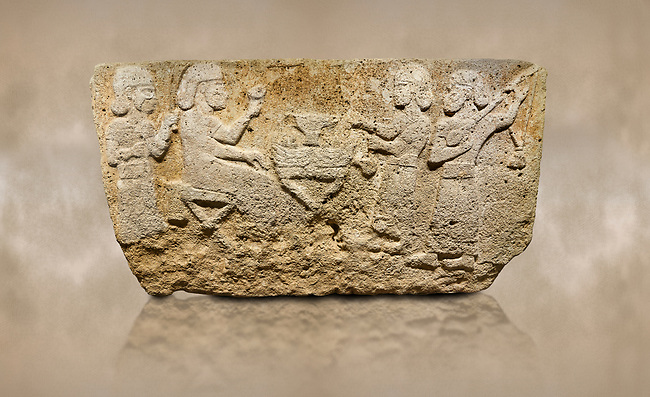 Photo of Hittite monumental relief sculpted orthostat stone panel from Water Gate Limestone, Karkamıs, (Kargamıs), Carchemish (Karkemish), 900-700 BC.  Anatolian Civilisations Museum, Ankara, Turkey.<br /> <br /> The figure sitting on a stool to the left of the table holds a goblet in his right hand which he raised upwards. Behind, there is a servant with a fan in his hand. On the other side of the table is another servant waits with a vessel in the hands. The rightmost figure plays a Saz (a stringed musical instrument) with the tassel on the handle. <br /> <br /> On a brown art background.