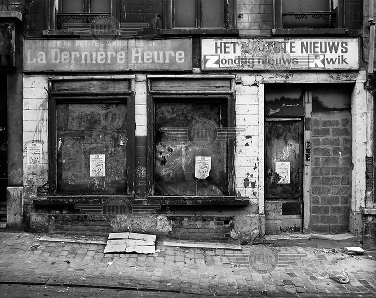 A borded up newsagent shop with signs for Flemish and French language publications.