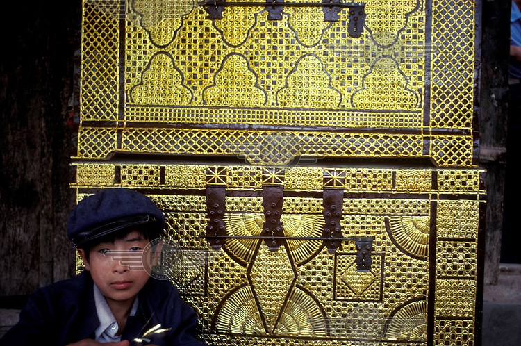 Young craftsman decorating chests with brass ribbon in Kashgar.