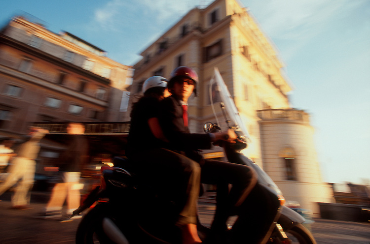 "Rome, Italy, A classic example of the ""motorini,"" the motor scooter set of Rome: A man and woman on a motor scooter at speed near Piazza di Spagna (the Spanish Steps) at sunset."