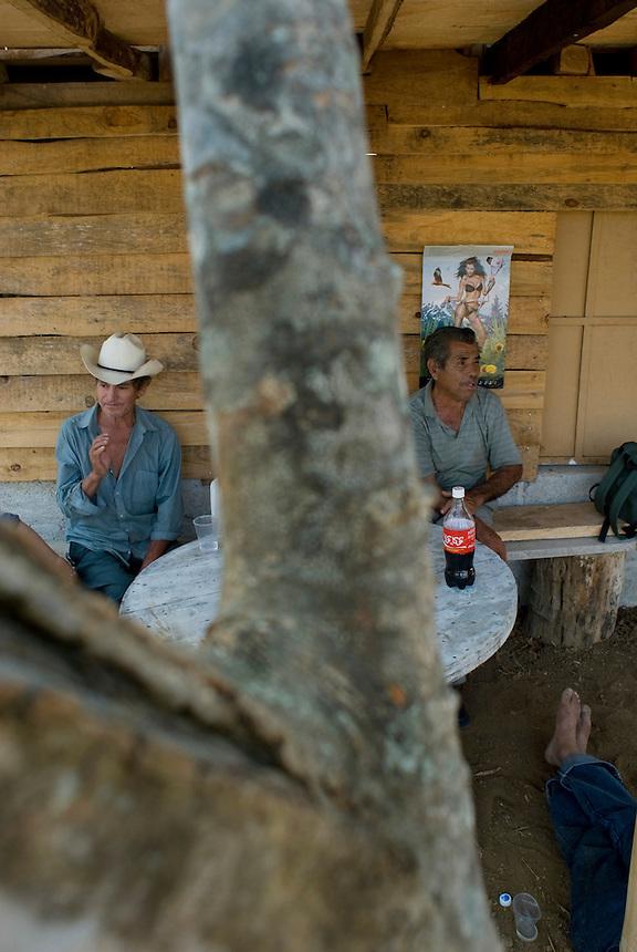 Men drinking in the shade of a wooden cabinMonte Blanco, Veracruz. April 4, 2008