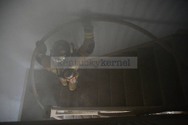 A firefighter lifts a hose up the stairs to the second story of Boyd Hall. The exercise focused on hose techniques for those seeking to become Officers in the Lexington and Georgetown fire department in Lexington, Ky., on Wednesday, January 15, 2014. Photo by Eleanor Hasken | Staff