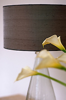 A contemporary lamp with a taupe linen shade and a pear-shaped glass base