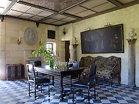 In the wine tasting room, a 17th century Dutch painting bought at auction hangs above a Regence settee covered in its original needlepoint upholstery; the table is 19th century, the walls are 18th century stone, and the floors are laid with 19th century tiles