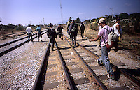 Inmigrants from Central America in Chiapas, Southern Mexico, before boarding a train in their attempt to reach the US border. They are the poorest persons among the inmigrants, they got to Mexico walking from Honduras, Guatemala or Nicaragua. Once in Mexico they can rest in shelters run by catholic priests before facing the dangerous train travel. In this step, they are often abused by police and gangs that steal the men and rape the women..Migrantes centroamericanos caminan entre las vías, en Ixtepec, Oaxaca, esperando el siguiente tren para seguir su camino a la frontera norte de México.