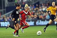 Canada forward Kelly Parker (15) goes pass Carli Lloyd (10).