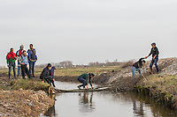 FRANCE, Calais: 17 December 2015 Refugees help each other cross a river after clashing with French riot police outside of the Euro Tunnel entrance in Calais this afternoon. Hundreds of refugees walked hours through Calais today to reach the Euro Tunnel from 'The Jungle' camp to try and get to England. Rick Findler  / Story