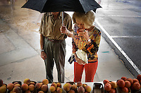 Ross Greenstreet (cq, left) holds an umbrella over his wife, Peggy Greenstreet (cq), so she can smell a peach at the Finley Farms booth at the White Rock Lake Farmers Market in Dallas, Texas, USA, Saturday, Sept. 12, 2009. Growing produce or buying locally grown vegetables and canning at home is a fun and healthy way to keep grocery costs down...CREDIT: Matt Nager for The Wall Street Journal