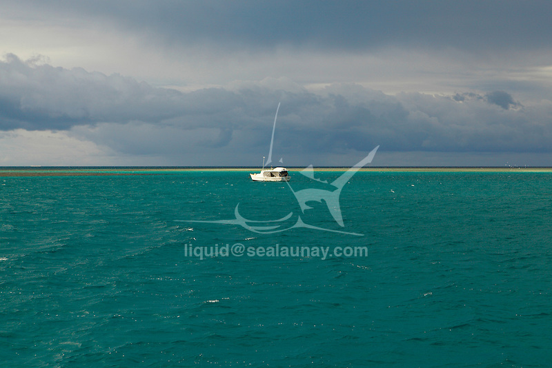 """a boat at anchor in a lagoon before a squall come at  the Isle of pines, New Caledonia.The Isle of Pines (French: Île des Pins; Kanak name: Kunyié) is an island located in the Pacific Ocean, in the archipelago of New Caledonia, an overseas territory of France. The island is part of the commune (municipality) of L'Île-des-Pins, in the South Province of New Caledonia. The Isle of Pines is often nicknamed l'île la plus proche du paradis (""""the closest island to Paradise"""") and is famous for snorkeling and scuba diving in and around its colorful lagoon. Many species of tropical fish and corals can be seen in the transparent water..The island is located around [show location on an interactive map] 22°37?S 167°29?E / 22.617°S 167.483°E / -22.617; 167.483Coordinates: 22°37?S 167°29?E / 22.617°S 167.483°E / -22.617; 167.483 and measures 15 km (9 miles) by 13 km (8 miles). It lies southeast of Grande Terre, New Caledonia's main island and is approximately 100 kilometres south-east of the capital Noumea. There is one airport (code ILP) with a 1,097-meter (3,600 ft) runway. The Isle of Pines is surrounded by the New Caledonia Barrier Reef..The inhabitants of the island are mainly native Melanesian Kanaks and the population is approximately 2,000 (estimated 2006) (1989 population 1,465)..The island is rich with animal life and is home to many unique creatures such as the Crested Gecko Rhacodactylus ciliatus and the world's largest gecko Rhacodactylus leachianus..The pic Nga is the island's highest point, at 262 meters (860 ft) elevation..The island was first discovered by Captain James Cook in 1774 on his second voyage to New Zealand. Captain Cook gave the island its name after seeing the tall native pines (Araucaria columnaris). It is said he never actually disembarked onto the island but as he saw signs of inhabitance (smoke) assumed it was inhabited. In the 1840s both Protestant and Catholic missionaries arrived, along with merchants seeking sandalwood..The French took possess"""