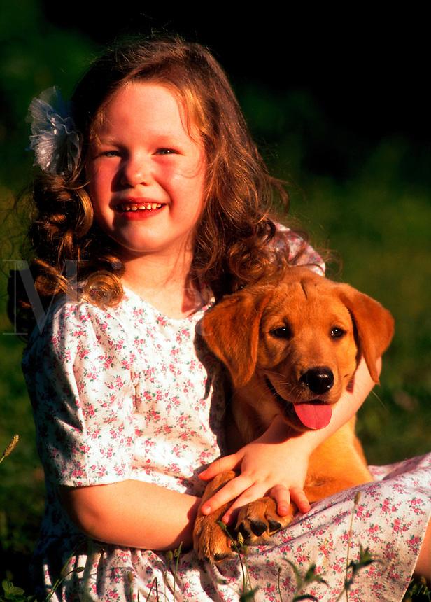 Young girl with yellow labrador retriever puppy.