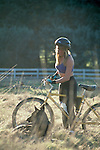 Woman and her dog take a break from mountain biking