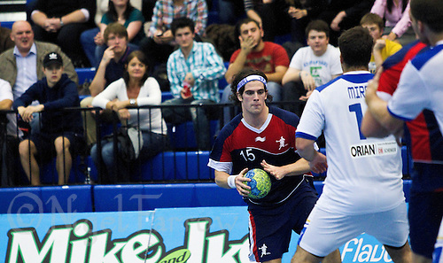 02 NOV 2011 - LONDON, GBR - Britain's Martin Hare (#15 - blue and red) looks for a way past Israel's Daniel Mircus (#14 - white) during the Men's 2013 World Handball Championship qualification match at the National Sports Centre at Crystal Palace .(PHOTO (C) NIGEL FARROW)