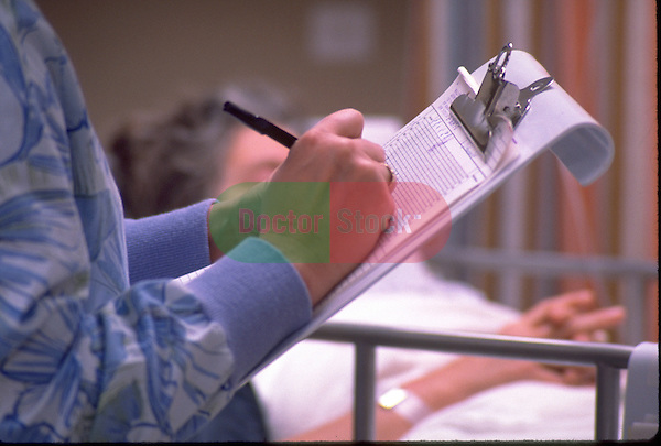 Nurse writing in chart in hospital