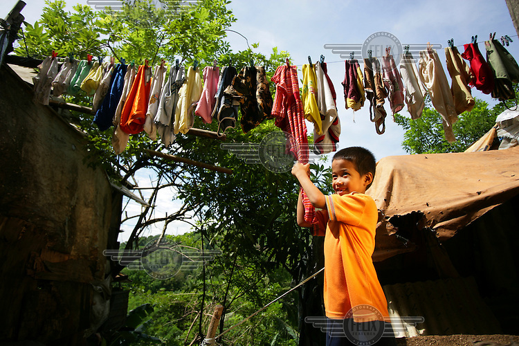14 year old Rex helps with the family's washing outside where he lives with his parents and nine siblings on the Olongapo Landfill site. He earns money by scavenging the site for up to ten hours a day, looking for saleable items.