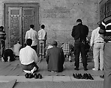TURKEY, Istanbul, rear view of men praying in Sultan Ahmed Mosque