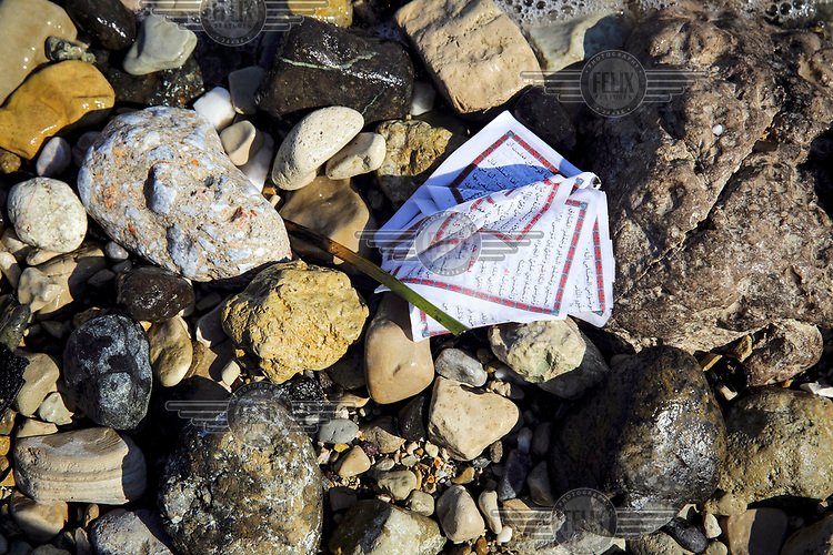 Soaked pages of Arabic text lie on the Mitilini shore.