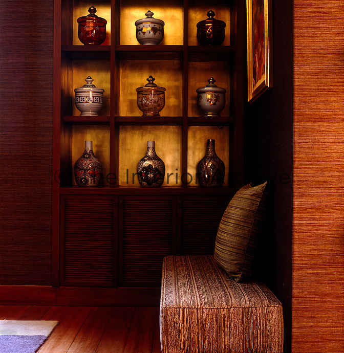 In one corner of the dining room an elegant set of shelves displays a collection of traditional ceramic and glass urns