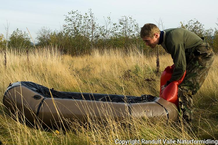 Mann blåser opp gummibåt (Alpacka raft) ----- Man inflating rubber boat