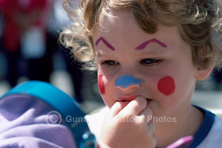 Young Child looking in Mirror at Painted Face (No Model Release Available)