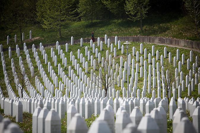 Eine junge bosnische Frau läuft an den Grabsteinen auf dem Potocari-Denkmal-Kirchhof entlang. / A young Bosnian woman is walking next to some of the tombstones at the Potocari memorial cemetary.