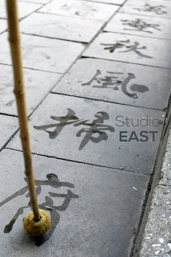 A calligrapher trains by writing Chinese characters with water in Beijing, China, on August 23, 2004. Photo by Lucas Schifres/Pictobank