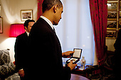Oslo, Norway - December 10, 2009 -- United States President Barack Obama looks at the Nobel Peace Prize medal at the Norwegian Nobel Institute in Oslo, Norway, Thursday, December 10, 2009..Mandatory Credit: Pete Souza - White House via CNP
