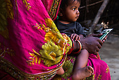28 year old Asha Devi with her 11 month daughter, Sharda in their house in Saptari, Nepal. <br /> Asha Devi got married when she was 14. She got pregnant after 6 months of her marriage. Her first child survived for 6 days, she woke up next to a dead baby. She was pregnant two months later. Asha Devi's 2nd daughter survived for 9 months and later died due to prolonged fever. 3 months after her daughter died, Asha was pregnant again and within w months, she had spontaneous abortion. She was pregnant with Radha Kumari mandal who was acutely malnourished. Radha was admitted when she was 36 months old on October, 20th 2013. MUAC - 110 mm, Weight - 7 kg, Height - 75 cm. Radha was discharged on Dec 6, 2013 - her MUAC at the time of discharge was 128mm, Weight 8.8kg and height- 75.5 cm. She consumed 100 sachets of RUTF and gained 5gm/day while on the programme. <br /> Rukmini, her second daughter was born a year after Radha was born. Rukmini was severely malnourished too. She was admitted on Feb 16th, 2014. Her MUAC was 119mm, weight - 11 kg, and height - 96 cm. Her third daughter Sharda is severely malnourished. Sharda is under RUTF.  <br /> Asha Devi is pregnant for the 7th time and is 6 months pregnant.