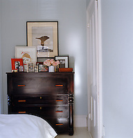 Detail of a wooden chest of drawers inthe bedroom with framed family photographs and prints
