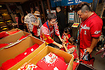 A staff member gives a Hiroshima Carp Central League Champions 2016 t-shirts to fans at Hiroshima Brand Shop TAU in Ginza on September 11, 2016, Tokyo, Japan. Hundreds of Carps fans lined up from early morning outside Hiroshima Brand Shop TAU to buy victory t-shirts after Hiroshima baseball team got its first Central League title in 25 years after beating the Yomiuri Giants 6-4 on Saturday, September 10. (Photo by Rodrigo Reyes Marin/AFLO)