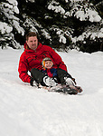 California, Lake Tahoe: Child and father enjoy snow play with sled at North Lake Tahoe Regional Park.  Photo copyright Lee Foster.  Photo # cataho107628