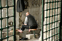 MAN CARRYING OUT HIS RITUAL WASHING BEFORE PRAYER OUTSIDE MOSQUE, ISTANBUL, TURKEY
