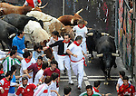 Participants run with Miuras bulls during the last bull run in the San Fermin Festival on July 14, 2014, in Pamplona, Basque Country. Every year, tens of thousands of people pack Pamplona's streets for a drunken kick-off to one os worls's best-known fiesta: the nine-day San Fermin bull-running festival. (Ander Gillenea / Bostok Photo)