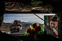 SAYADABAD, WARDAK PROVINCE, AFGHANISTAN - NOVEMBER 3, 2013: Afghan Army and Police, seen through the front window of a humvee, travel down highway 1 near Sayadabad on November 3, 2013 in Sayadabad, Wardak Province, Afghanistan.